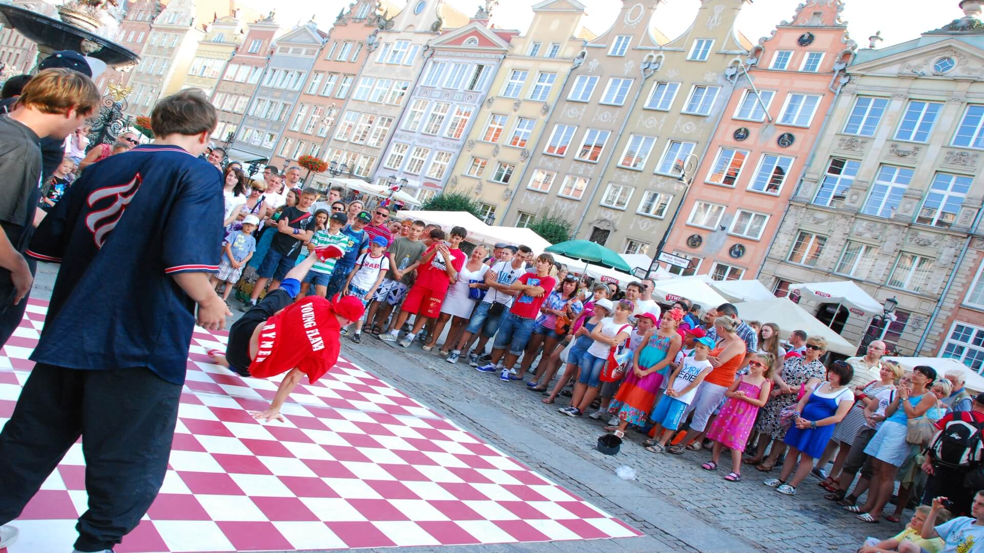 A hip-hop performance during summertime. Lots of artists are performing in the proximity of Neptune's Fountain and Artus Court. On the background you have the historical houses owned by the Polish kings.